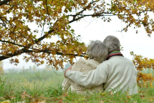 cute-elderly-couple-sitting-on-grass
