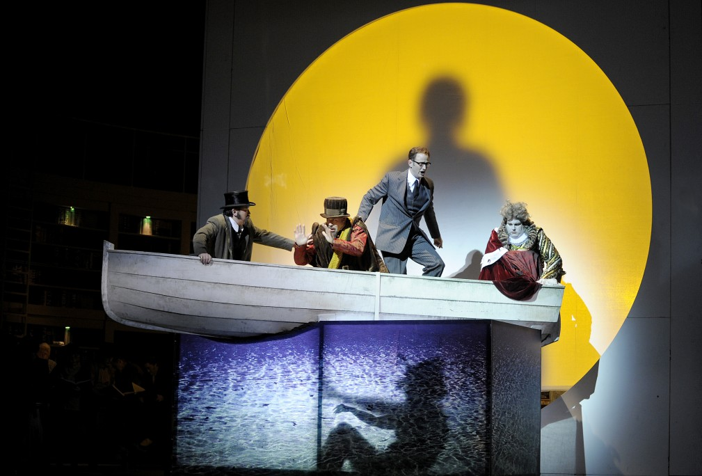 A photo of Keith Warner's production of Thomas Ades's The Tempest at Opera Frankfurt - the characters are in a rowing boat in front of a large yellow moon.