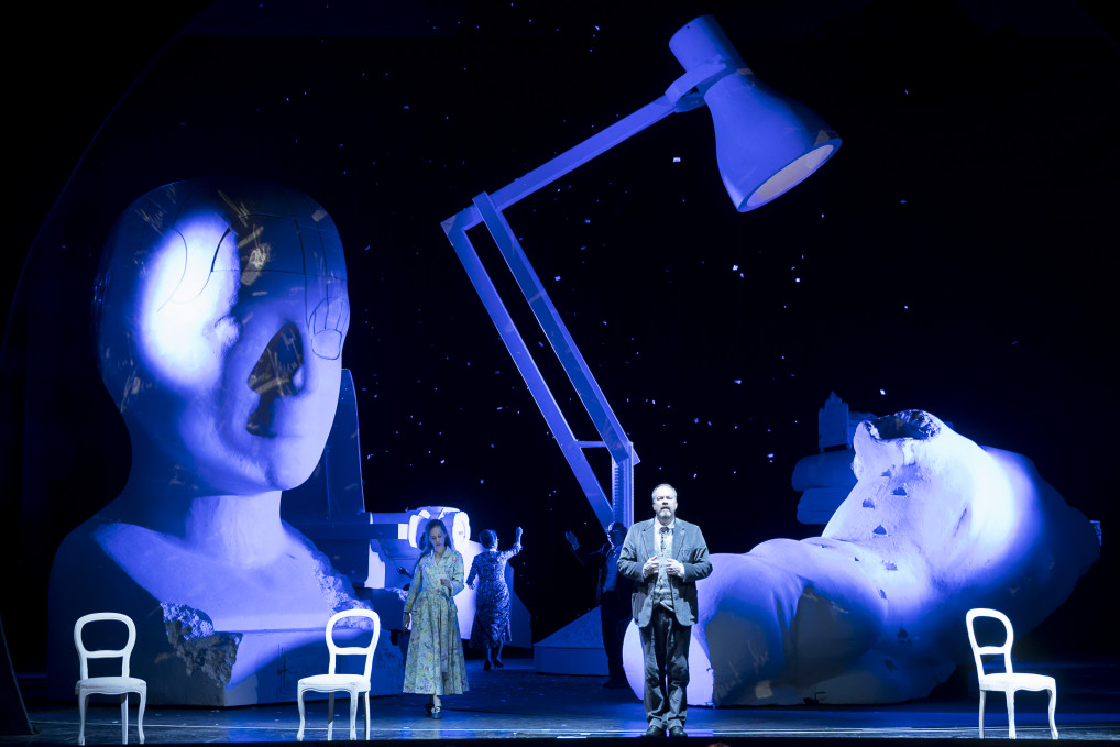 Keith Warner's production of Elegie für junge Liebende (Elegy for Young Lovers) at Vienna's Theater an der Wien. A man and woman lit in blue stand in front of a giant desk lamp and phrenology head