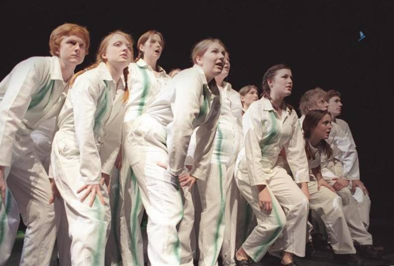 Glyndebourne Youth Opera performing Elemental in 2004 - the group of young singers wear white suits with a single green stripe