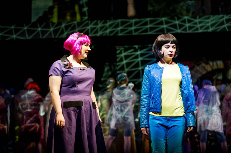 Freya Wynn-Jones performing in Imago at Glyndebourne, she wears a purple dress and a bright pink wig.
