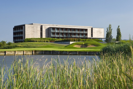 Exterior view across the lake of the Double Tree by Hilton Emporda Hotel