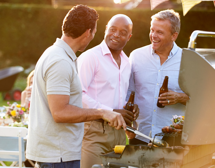 image contains three men grilling together