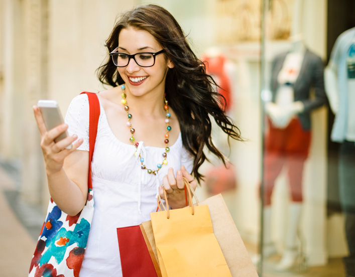 image contains woman shopping and using mobile phone