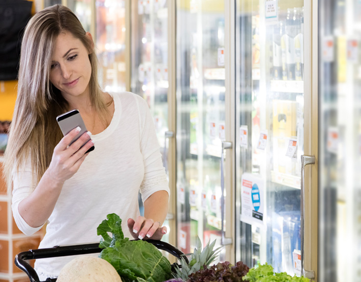image contains a female consumer using her phone while she is shopping