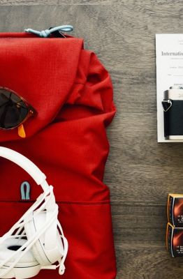 Foto aérea de uma mochila, óculos, fone de ouvido, camera, documentos e filme sob uma mesa. Photo via Visual hunt