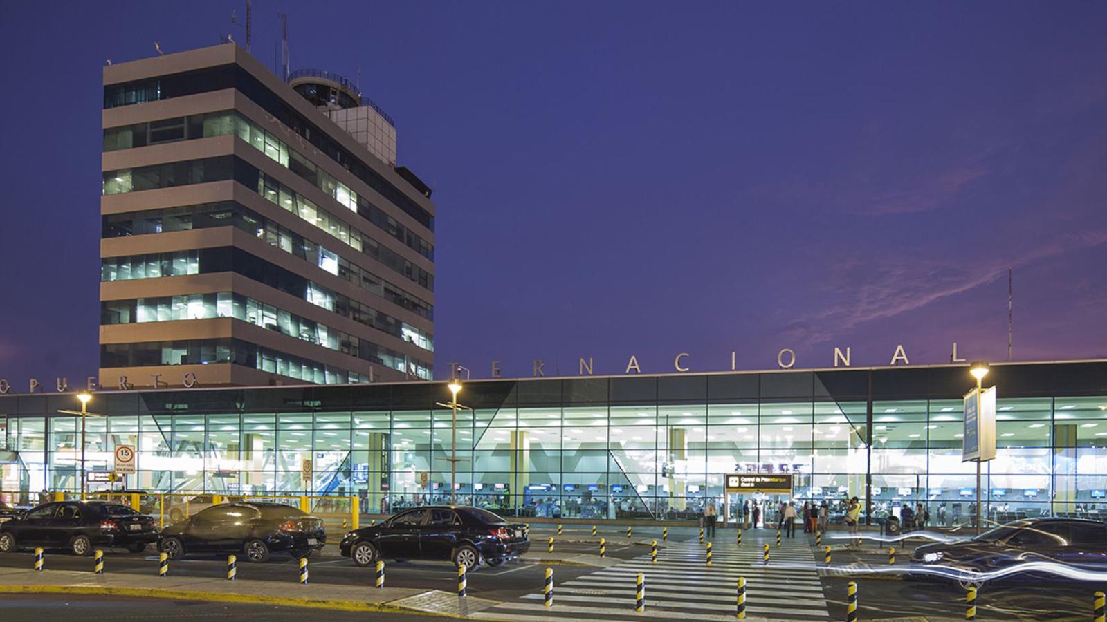 Entrada do Aeroporto Internacional Jorge Chavez ao anoitecer com carros passando em frente deixando rastro de luz