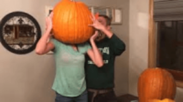 girl's head stuck in pumpkin