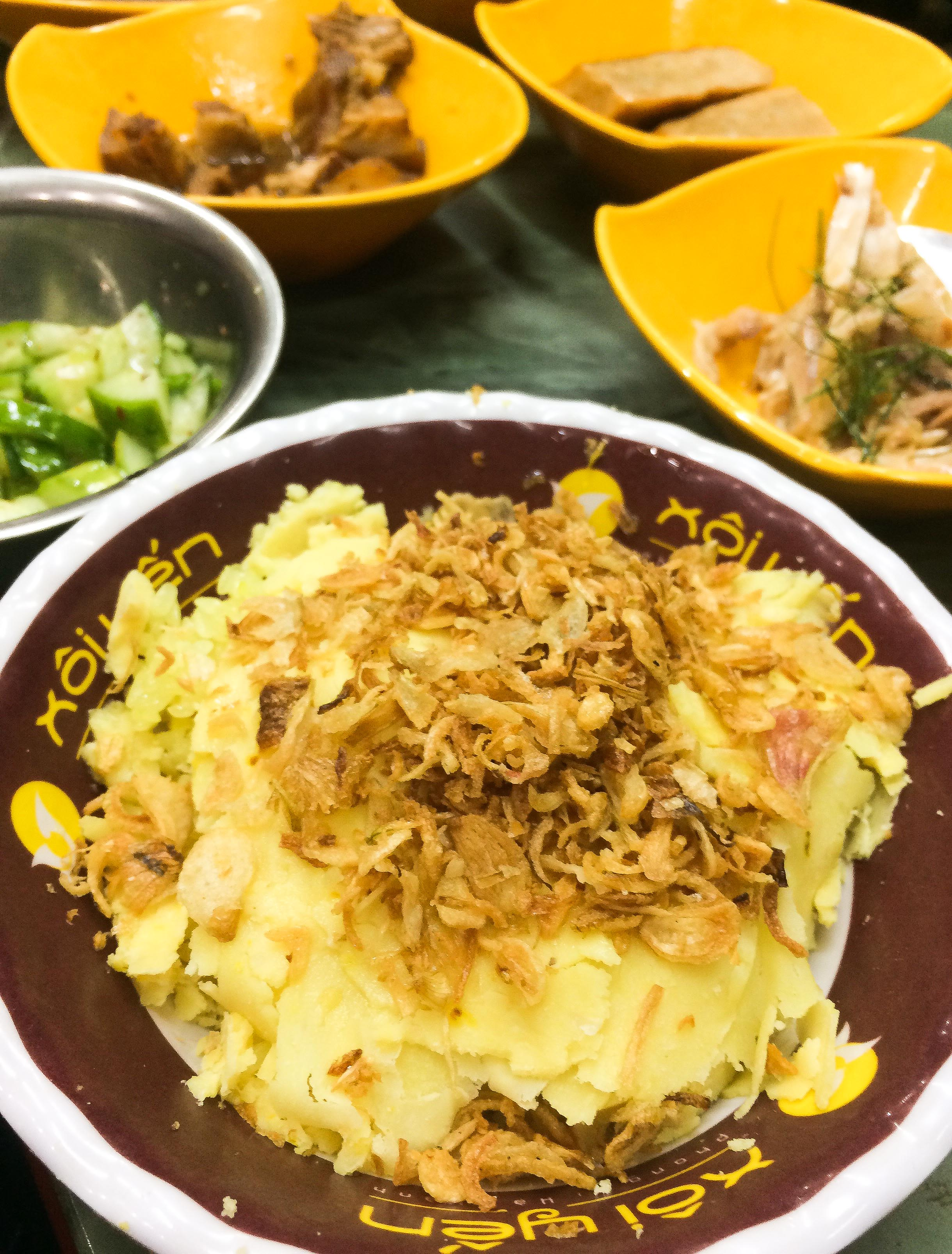 xôi thap cam is a bowl of sticky rice, covered with shaved mung beans, fried onions, and chicken fat drizzled over top