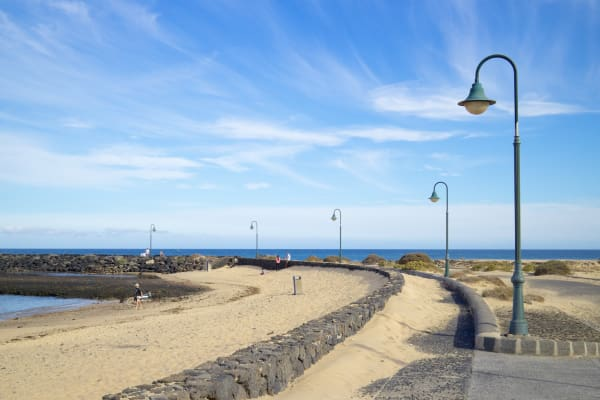 las cucharas beach walk with typical street lamps on lanzarote island
