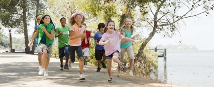Children running beside a lake