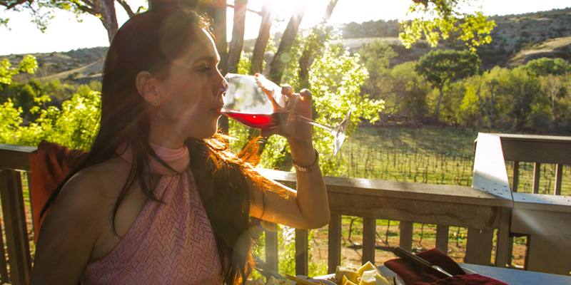 A woman enjoys a glass of wine among the vineyard at Page Springs Cellars in Cornville, Arizona