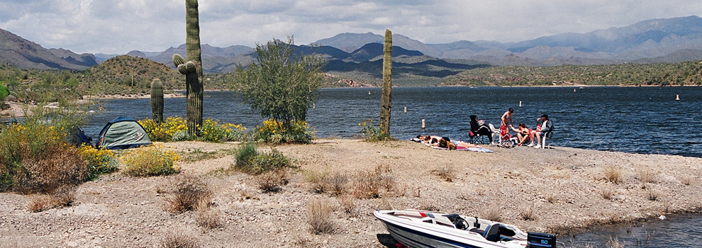 A group lounges on the shore of Lake Pleasant, their boat docked near them and the mountains in the background