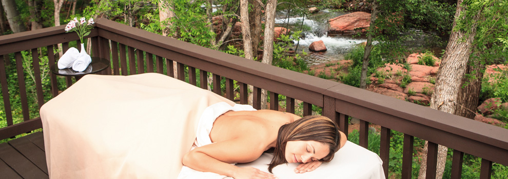 A woman lays outside on a massage table beside a creek at L'Auberge in Sedona