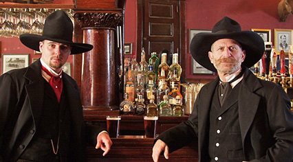 Two men in Western attire stand at the bar in Prescott Saloon