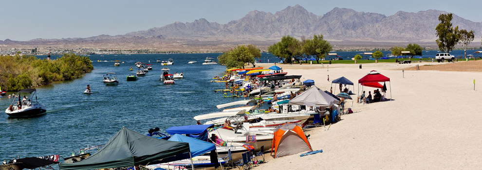 Boats line the shore and play in the water at Lake Havasu State Park