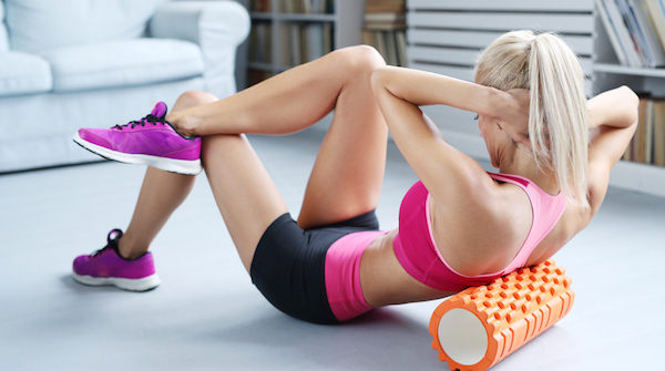 Woman in athletic gear using orange foam roller for self-massage and recovery