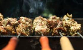 Brochettes de porc au thym garnies de tomates et d'oignons grillés