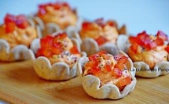 Amuse bouche garni de confit de poivron rouge sur un lit de raifort parsemé de graines de sésame noir