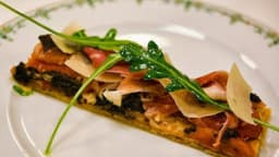 Feuilleté - bruschetta, garni de jambon cru, tapenade, artichaut, tomates et parmesan