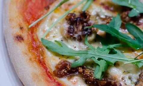 Pizza à la raclette, aux figues sèches, aux noix et à la roquette