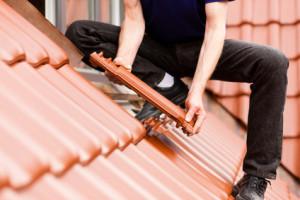Dachdecker deckt Dach mit Dachziegel ein.