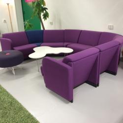 Svängd soffa i lila och en sits i blått. Varje sits är ca 67 cm bred. Totalt ca 350 cm.