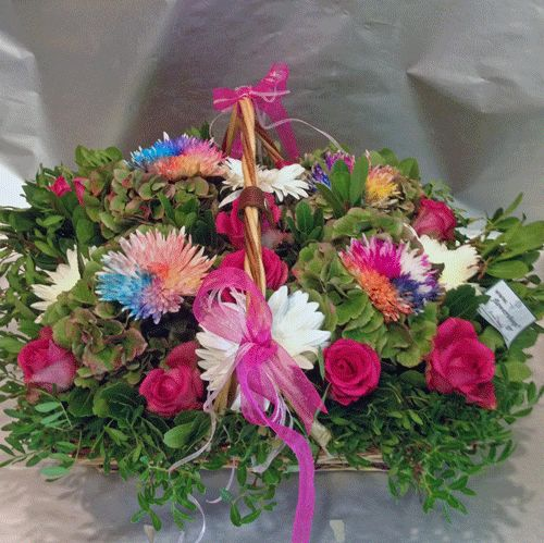 Flower arrangement with rainbow flowers in big basket with autumn flavor