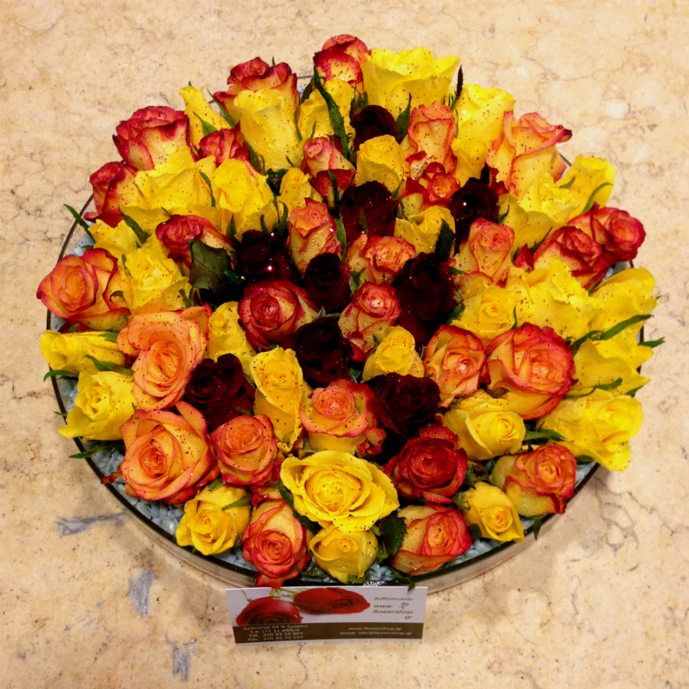 Mixed colored roses in glass with colored sand decoration