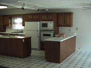Kitchen with two countertops and a gap between to walk in. Countertop is white and appliances are white. Cabinets are brown.