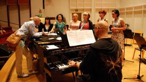 Mies soittaa pianoa jonka ympåärillä on ihmisiä laulamassa
