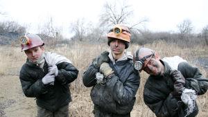 Kolme nuorta poikaa kaivoskamppeet päällä