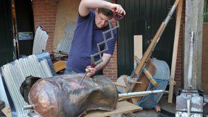 Soitinrakentaja tekemässä selloa peltiromusta