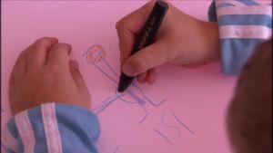 Lapsi piirtää kuvaa isästä.