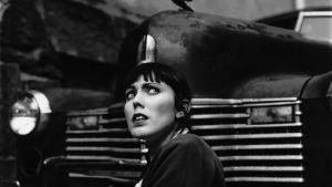 mustavalkoisessa kuvassa ahdistuneen näköinen nainen auton edessä
