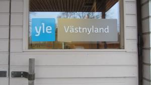 Skylten på Yle Västnylands dörr.
