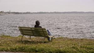 Kvinna sitter på parkbänk och tittar ut över havet
