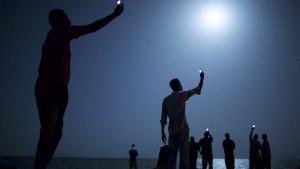 World Press Photo of the Year 2013. Afrikanska migranter i Djibouti försöker nå en mobilsignal från Somalia där priserna är billigare.