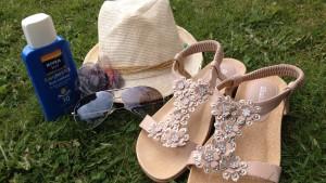 Sommarsandaler, solglasögon och solkräm och en hög på gräsmattan