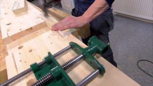 Jim sågar till och fäster en lämplig träbit som ska fungera som den ena skivan bänklkämmaren spänns mot