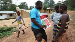 En FN-anställd berättar för några invånare i Liberia hur man undviker ebola.