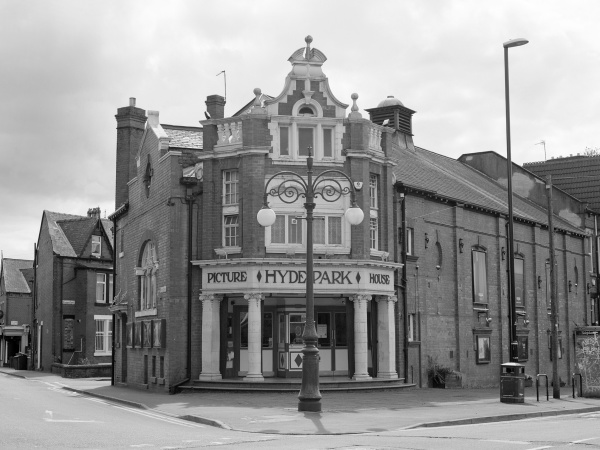 Exterior shot of Hyde Park Picture House with terraced houses visible in distance.