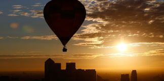 A hot air balloon rises into the early morning sky in front of the Canary Wharf financial district of London