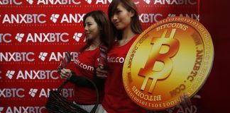 Attendants pose with a bitcoin sign during the opening of Hong Kong's first bitcoin retail store February 28, 2014