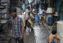 Residents walk in an alley in Dharavi, one of Asia's largest slums, in Mumbai