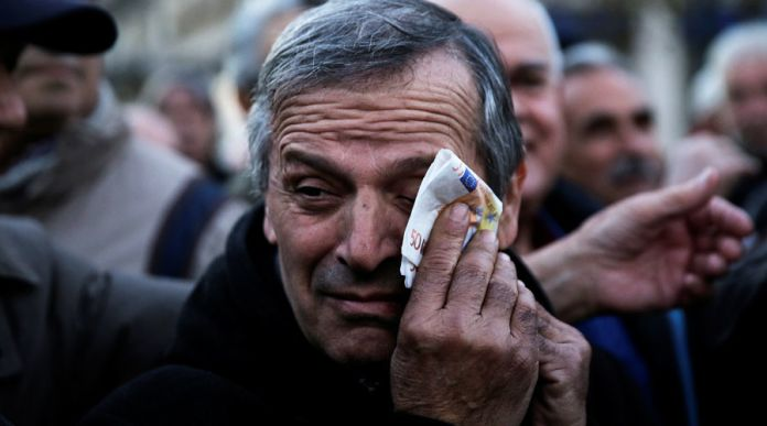 A Greek pensioner wipes his face with a fake euro banknote during a demonstration against government policies affecting pensioners in Athens