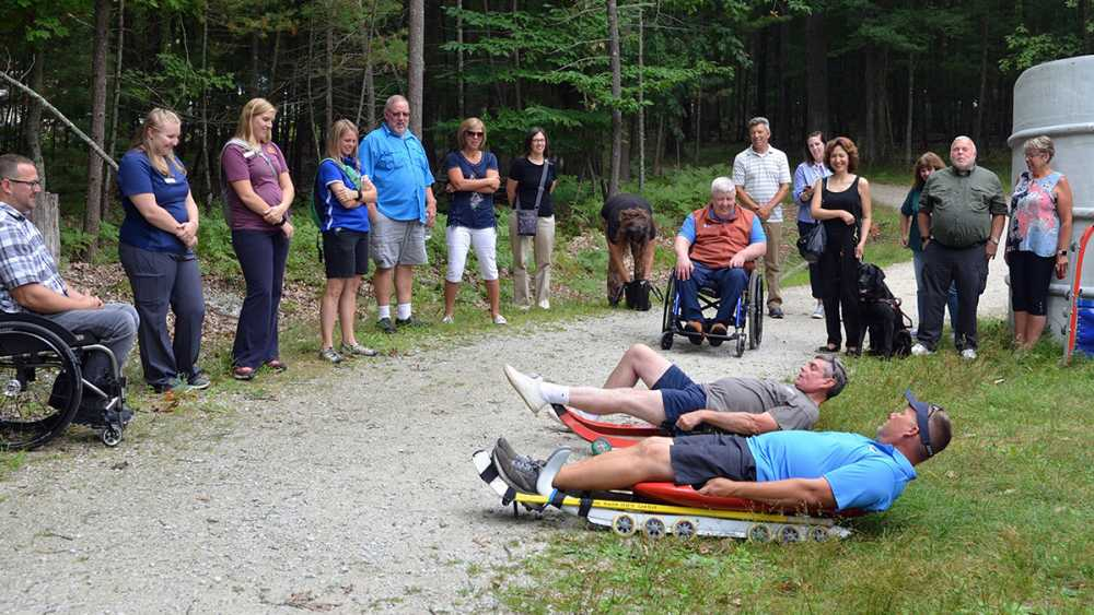 Two men are instructed on how to use the accessible luge at Muskegon State Park
