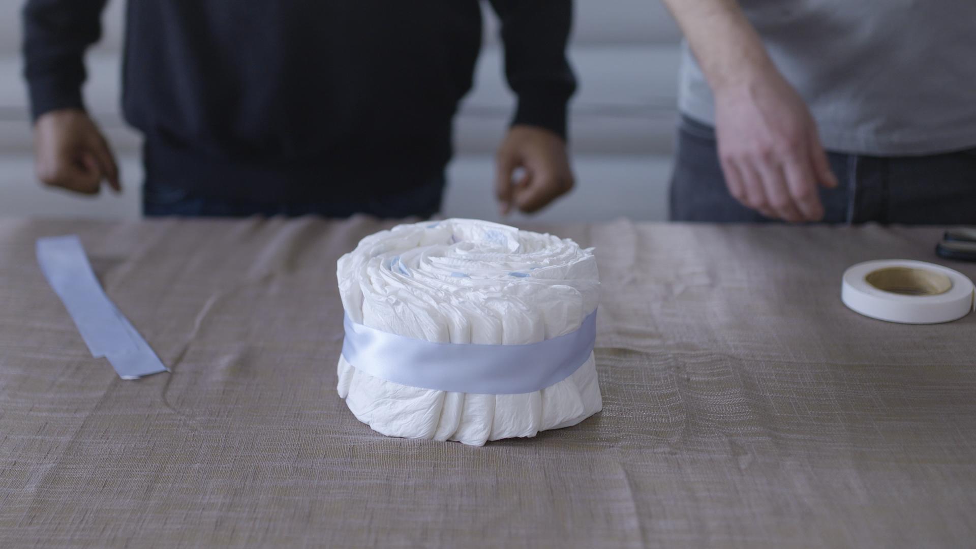 Klipp til silkebåndet og trekk det rundt hjulet, slik at det dekker til strikken. Fest det med dobbelsidig teip.
