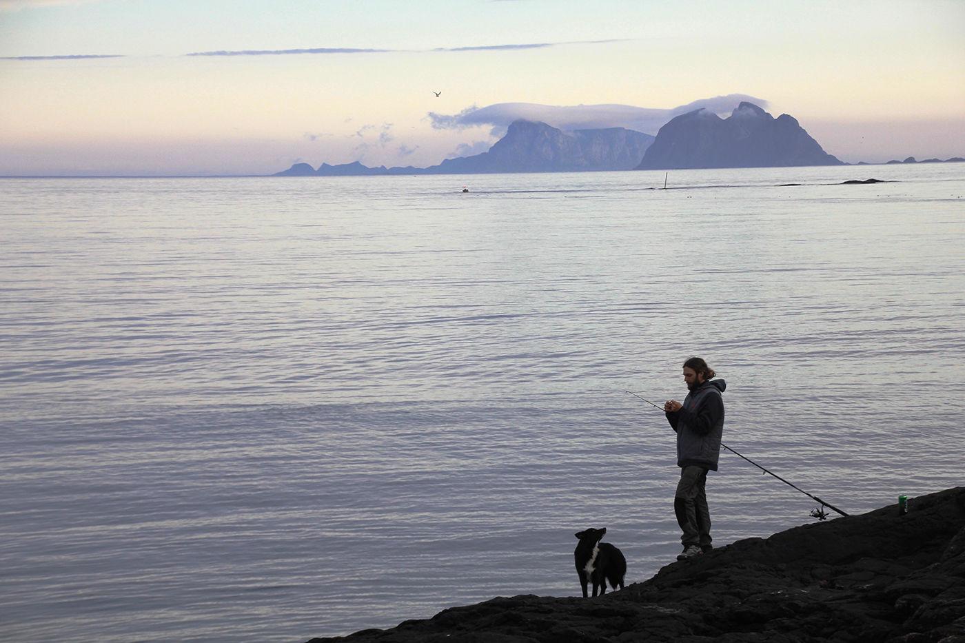 Niklas og Thea fisker middag med Værøy og Mosken i bakgrunnen.