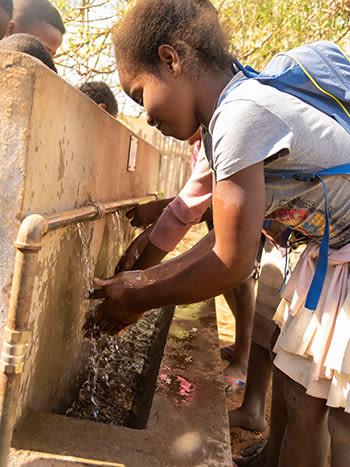 En skolejente vasker hendene i rent vann.